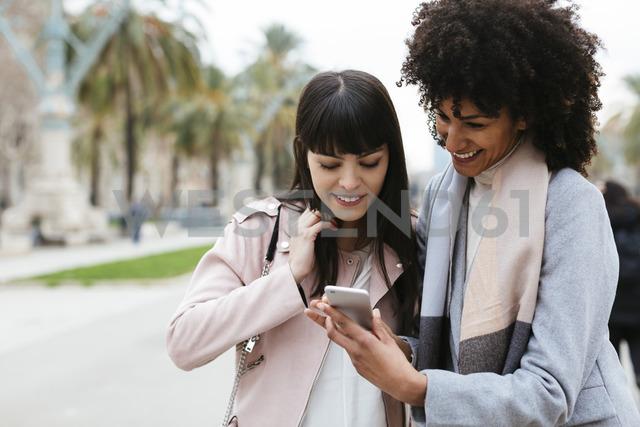 Spain, Barcelona, two happy women looking on cell phone on promenade - EBSF02150 - Bonninstudio/Westend61