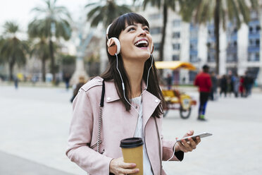 Spain, Barcelona, laughing woman with coffee, cell phone and headphones in the city - EBSF02153