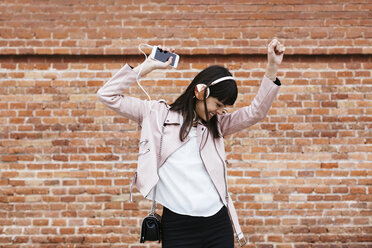Happy woman with cell phone listening to music on headphones at brick wall - EBSF02156
