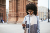 Spain, Barcelona, smiling woman with cell phone and earphones in the city - EBSF02159