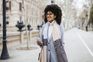 Spain, Barcelona, smiling woman with cell phone and earphones in the city - EBSF02162