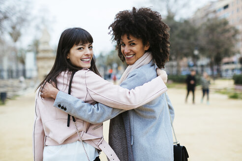 Spain, Barcelona, portrait of two happy women in city park embracing turning round - EBSF02180