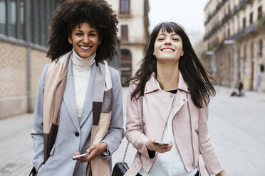 Spain, Barcelona, portrait of two female friends with cell phones in the city - EBSF02189