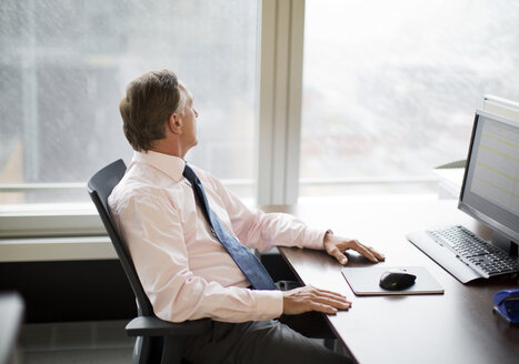 Businessman gazing out window in office - CAIF01829
