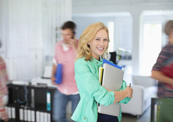 Businesswoman carrying folders in office - CAIF01844