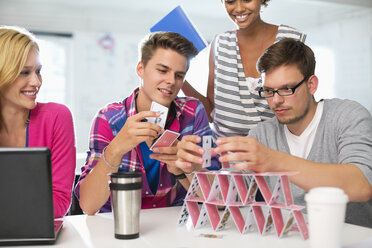 Business people making house of cards in office - CAIF01847