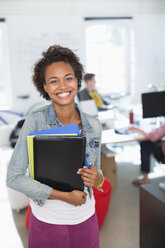Businesswoman carrying folders in office - CAIF01850