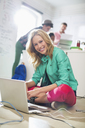 Businesswoman using laptop on floor in office - CAIF01859