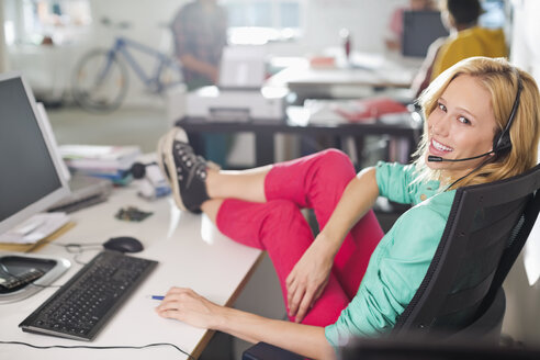 Businesswoman wearing headset at desk - CAIF01865