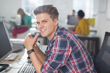 Businessman smiling at desk - CAIF01871