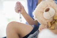 Boy taking insulin injection in leg - CAIF01886