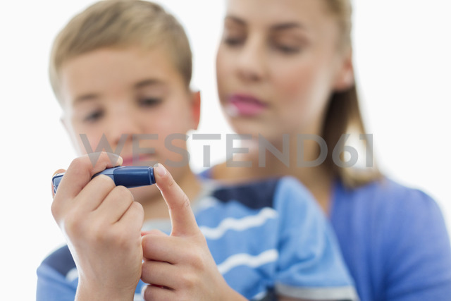 Mother helping son test blood sugar - CAIF01892