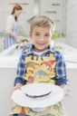 Boy covered in flour holding cake in kitchen - CAIF01934
