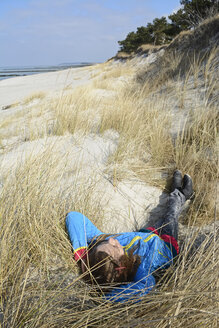 Germany, Hiddensee, girl relaxing in the dunes - BFRF01822