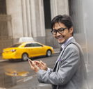 Businessman using cell phone on city street - CAIF02052