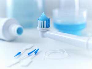 Close up of toothpaste on electric toothbrush - CAIF02082