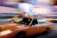 Blurred view of taxi on city street at night - CAIF02115