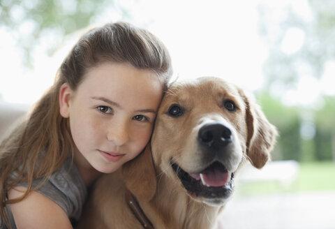Girl hugging dog indoors - CAIF02193
