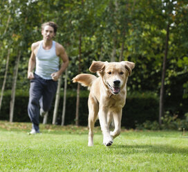 Man running with dog in park - CAIF02211