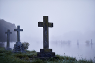 Crosses on gravestones in ethereal flooded foggy cemetery - CAIF02238