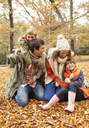 Family playing together in autumn leaves - CAIF02295