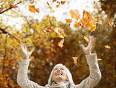 Older woman playing in autumn leaves - CAIF02301