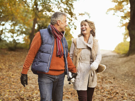Older couple walking together in park - CAIF02304