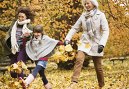 Three generations of women playing in autumn leaves - CAIF02319