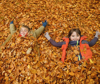 Children laying in autumn leaves - CAIF02340