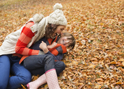 Mother and daughter playing in autumn leaves - CAIF02346