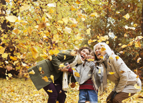 Three generations of women playing in autumn leaves - CAIF02349
