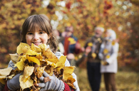 Girl playing with autumn leaves in park - CAIF02355