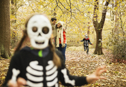 Children in skeleton costumes playing in park - CAIF02367