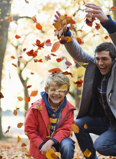Father and son playing in autumn leaves - CAIF02373