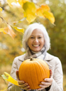 Older woman holding pumpkin in park - CAIF02379
