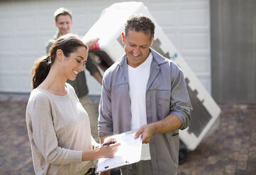 Woman signing for delivery in driveway - CAIF02409