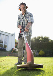 Man using weed whacker in backyard - CAIF02415