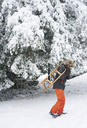 Boy carrying wooden sled in snow - CAIF02442