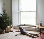 Boy playing with train by Christmas tree - CAIF02448