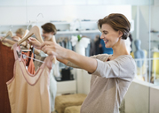 Woman shopping for clothes in store - CAIF02460