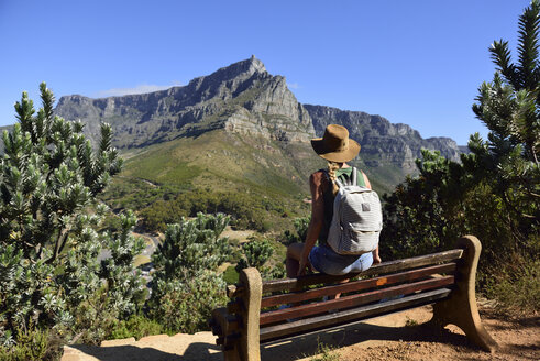 South Africa, Cape Town, woman sitting on bench during hiking trip to Lion's Head - ECPF00219
