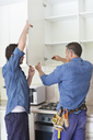Workers installing cabinets in kitchen - CAIF02528