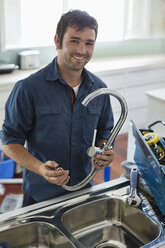 Plumber working on kitchen sink - CAIF02537