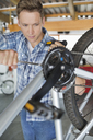 Man working on bicycle in shop - CAIF02552