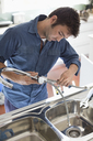 Plumber working on kitchen sink - CAIF02555
