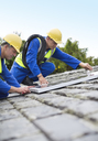 Workers installing solar panels on roof - CAIF02558