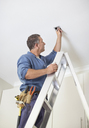 Electrician working on ceiling lights - CAIF02567