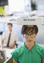 Businesswoman wearing 'out of order' sign - CAIF02612