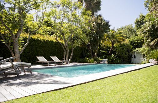 Lawn chairs and swimming pool in backyard - CAIF02630