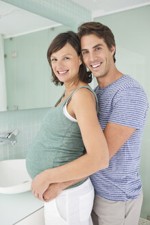 Smiling couple hugging in bathroom - CAIF02705